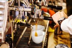 Sirva el café de colada de la mano del ` s en las tazas de cerámica blancas Imagen de archivo