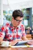 Sirva el café de consumición en la lectura del café de la calle en el dispositivo de la tableta fotografía de archivo libre de regalías