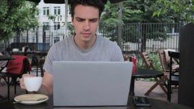 Sirva el café de consumición y el trabajo en el ordenador portátil mientras que se sienta en terraza del café fotos de archivo