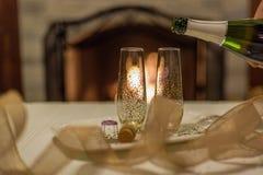 sirva el champán de colada en el vidrio delante de la chimenea foto de archivo libre de regalías