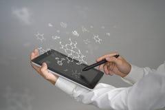 Sirva el científico con PC y la aguja de la tableta o la pluma que trabaja con fórmulas químicas en fondo gris Imagen de archivo