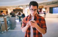 Sirva el control el smartphone del fondo de la alameda de compras Fotografía de archivo libre de regalías