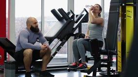 Sirva el donante de la botella de agua potable fresca a la mujer durante entrenamiento activo en gimnasio almacen de video