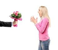 Sirva el donante de un manojo de flores y de mujer sorprendida Fotos de archivo libres de regalías