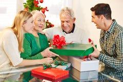 Sirva el donante del regalo a su madre en la Navidad fotografía de archivo libre de regalías