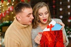 Sirva el donante presente a su muchacha el día del ` s de la tarjeta del día de San Valentín Foto de archivo libre de regalías