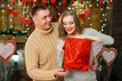 Sirva el donante presente a su muchacha el día del ` s de la tarjeta del día de San Valentín Fotos de archivo