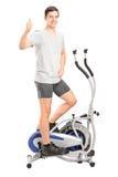 Sirva el ejercicio en una máquina cruzada del instructor y el donante del pulgar para arriba Foto de archivo libre de regalías
