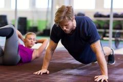 Sirva el ejercicio y hacer del tablón recto del brazo en gimnasio Fotografía de archivo