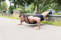 Sirva el entrenamiento y el ejercicio haciendo pectorales en el parque imagen de archivo