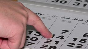 Sirva el finger que muestra el día 14 de febrero en el calendario de papel metrajes