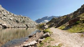 Sirva el funcionamiento en el sendero en paisaje idílico de la montaña con el lago cristalino del agua, el pico de alta montaña y almacen de video