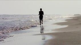 Sirva el funcionamiento en la playa en la puesta del sol