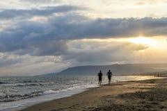 Sirva el funcionamiento en la playa en la puesta del sol foto de archivo