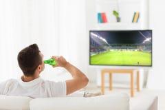 Sirva el juego de fútbol de observación en la TV y la cerveza de consumición imagen de archivo libre de regalías