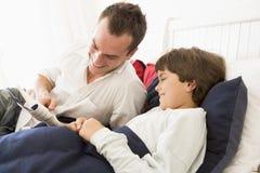 Sirva el libro de lectura al muchacho joven en la sonrisa de la cama Imágenes de archivo libres de regalías