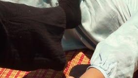 Sirva el massagiste que hace estirando masaje a la mujer al aire libre Mujeres que consiguen curso tailandés del masaje del cuerp metrajes