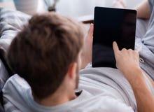 sirva el medios contenido de observación en una tableta que se sienta en un sofá Imagen de archivo