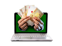 Sirva el outlaptop que viene de las manos que sostiene billetes de banco y naipes euro del póker del as Imagenes de archivo