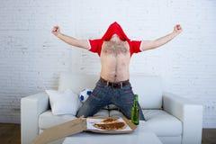 Sirva el partido de fútbol de observación en la TV en el jersey de equipo que celebra el salto feliz loco de la meta en el sofá Foto de archivo
