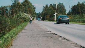 Sirva el paseo a lo largo del camino en campo con la placa de la cartulina hitchhiking Viajes metrajes