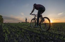 Sirva el paseo una bicicleta en puesta del sol y situación y observación del hombre Montar una bicicleta en la puesta del sol Con foto de archivo libre de regalías