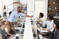Sirva el paso del documento a través del escritorio en una oficina abierta ocupada del plan Imagenes de archivo