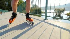 Sirva el patinaje en la trayectoria de asfalto en el puente del lago Patinaje en línea al aire libre Ciérrese encima de la visión almacen de metraje de vídeo