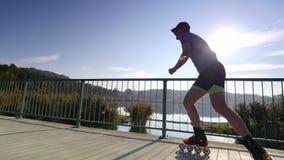 Sirva el patinaje en la trayectoria de asfalto en el puente del lago Patinaje en línea al aire libre Ciérrese encima de la visión metrajes