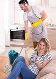 Sirva el piso que aljofifa mientras que mujer que descansa sobre el sofá fotografía de archivo libre de regalías