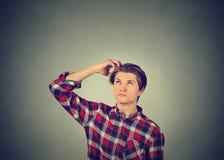 Sirva el rasguño de la cabeza, pensando en algo, mirando para arriba Imagen de archivo libre de regalías