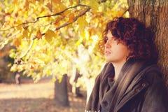 Sirva el retrato que se coloca cerca del árbol, oudoor en parque del otoño Imagenes de archivo