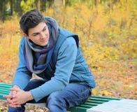 Sirva el retrato que se sienta en parque del otoño en un banco Foto de archivo