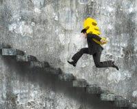 Sirva el símbolo euro de oro que lleva que corre en las escaleras concretas viejas Imagen de archivo