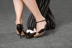 Sirva el ` s y los pies femeninos que bailan tango con las trayectorias de recortes Imagen de archivo