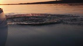 Sirva el salto del yate en el río en la puesta del sol almacen de video