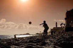 Sirva el salto e intentar coger de la bola de un sho del fútbol de la playa imagenes de archivo