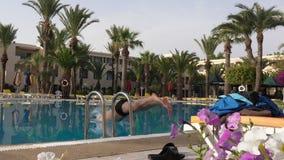 Sirva el salto en agua en piscina del hotel, cámara lenta almacen de video