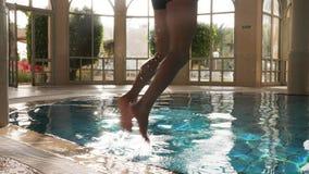 Sirva el salto y zambullirse con el chapoteo en piscina interior metrajes