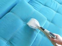 Sirva el servicio del sofá que limpia con la aspiradora, opinión del limpiador del hogar desde arriba Imagen de archivo