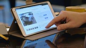 Sirva el sitio de exploración de eBay que busca el coche usado de Tesla usando la PC de la tableta en café almacen de metraje de vídeo
