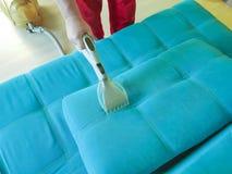 Sirva el sitio del servicio del sofá que limpia con la aspiradora, opinión del limpiador del hogar desde arriba Imagen de archivo