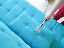 Sirva el sitio nacional, opinión del servicio del sofá que limpia con la aspiradora del limpiador del hogar desde arriba Foto de archivo libre de regalías