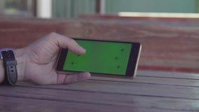 Sirva el smartphone del movimiento en sentido vertical de la mano del ` s con la pantalla verde almacen de metraje de vídeo