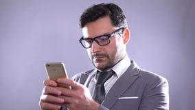 Sirva el SMS que manda un SMS con en el teléfono elegante en la noche en ciudad Hombre de negocios joven hermoso que usa la sonri almacen de video