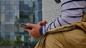 Sirva el SMS que manda un SMS usando el app en el teléfono elegante en la ciudad HD almacen de video