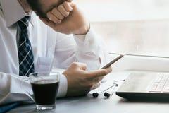 Sirva el SMS que manda un SMS usando el app en el teléfono elegante en la noche en ciudad Manos Fotos de archivo libres de regalías