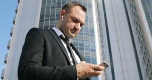 Sirva el SMS que manda un SMS usando el app en el teléfono elegante en ciudad Hombre de negocios joven hermoso usando la sonrisa  metrajes