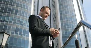 Sirva el SMS que manda un SMS usando el app en el teléfono elegante en ciudad Hombre de negocios joven hermoso usando la sonrisa  almacen de video