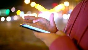 Sirva el SMS que manda un SMS usando el app en el teléfono elegante en la noche en ciudad Cierre para arriba almacen de metraje de vídeo